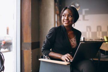Mulher trabalhando em um computador dentro de um bar